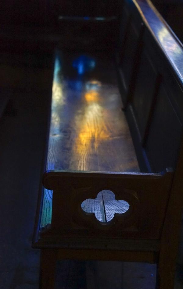 오래된 나무 의자 바닥에 건너편 스테인드글라스 빛이 비쳐 사람 모습이 언뜻 보인다. 사진_조현주