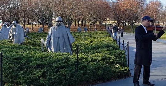 지난달 15일 미국 워싱턴 D.C. 한국전 참전 용사 기념비 앞에서 연주하는 원형준 음악감독 ⓒ린덴바움