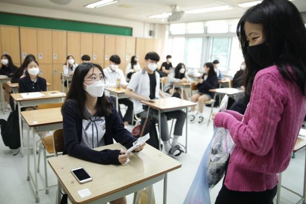20일 오전 경기도 성남시 수내등학교에서 코로나19로 미뤄진 지 80일만에 등교한 고3학생은 담임 선생님이 나눠주는 마스크와 손소독제를 받고 있다. ⓒ홍수형 기자