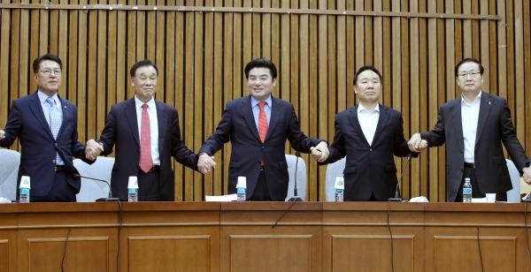 원유철 미래한국당 대표가 5월 26일 서울 여의도 국회에서 열린 당선인 합동회의에서 참석자들과 손을 맞잡고 있다.