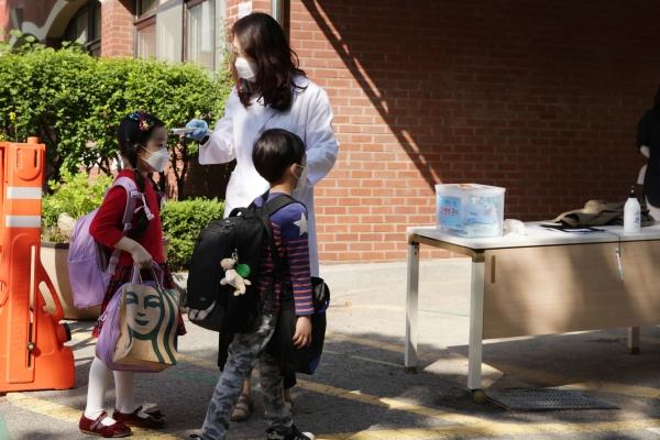 27일 오전 경기도 성남시 당촌초등학교 1학년 학생들은 올해 첫 등교 하며 입구에서 코로나19 예방을 위해 열 체크를 받고 있다. ⓒ홍수형 기자