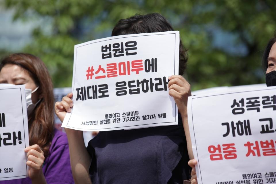 """한국여성의전화가 주최한 '용화여고 스쿨미투 사법정의 실현' 기자회견에서 한 참가자는 """"법원은 #스쿨미투에 제대로 응답하라""""라고 쓰여 있는 팻말을 들고 있다. ⓒ홍수형 기자"""
