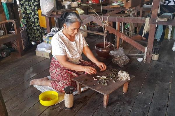 연꽃줄기에서 실을 뽑는 여성 작업자. ©조용경
