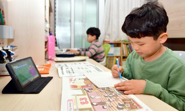 지난 4월 20일 광주 남구 봉선동 한 가정집에서 한 초등학교 1학년·3학년 학생이 온라인 개학에 맞춰 EBS 강의를 듣고 있다. ©뉴시스·여성신문