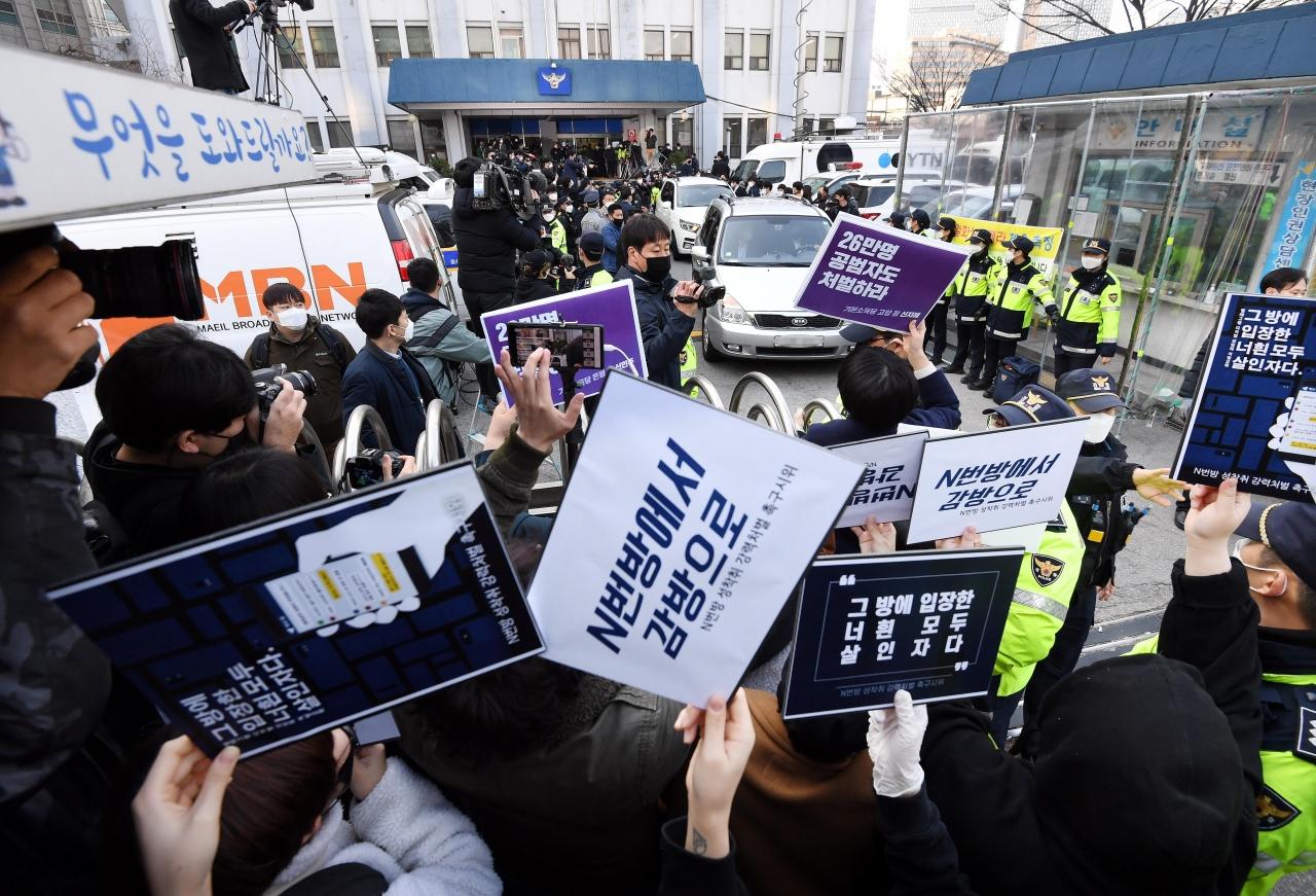 성들의 성 착취물을 제작 및 유포한 혐의를 받는 '박사방' 운영자 조주빈이 탄 차량이 서울 종로경찰서를 나와 검찰 유치장으로 향하자 시민들이 조주빈의 강력처벌을 촉구하며 피켓 시위를 하고 있다. 2020.03.25.<br>