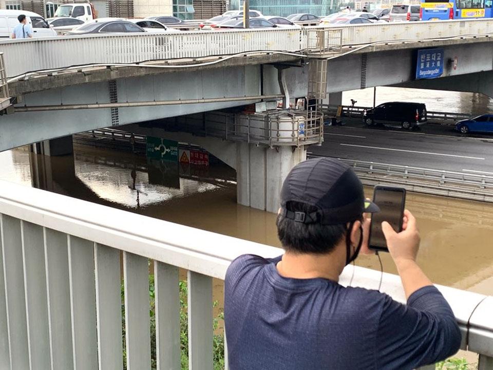 이틀째 계속되는 장마비로 한강 수위 상승으로 서울 서초구 잠수교는 전면 통제 중인 모습을 지나가던 한 시민이 촬영 중이다. ⓒ홍수형 기자