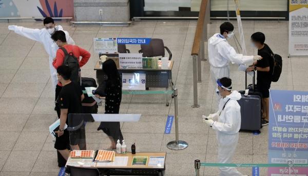 23일 인천국제공항 제1터미널로 입국한 여행객들이 방호복을 입은 관계자로부터 안내를 받고 있다. Ⓒ여성신문·뉴시스