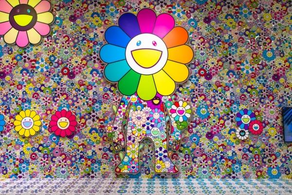 """Installation view Takashi Murakami at """"MURAKAMI vs MURAKAMI"""" in JC Contemporary, 2019 ©Takashi Murakami/Kaikai Kiki Co., Ltd. All Rights Reserved.Tai Kwun. Photography: Alex Maeland ©Hypebeast최고운 큐레이터= 무라카미 다카시의 대표 캐릭터인 '꽃'은 밝게 웃는 모습과 다양한 컬러로 여성스러움과 소녀적인 감성을 보여준다. 화면을 보면 헤아릴 수 없을 정도로 방대한 양의 꽃들을 벽면 가득 채워 그 위에 입체적인 꽃을 설치했다. 귀여운 캐릭터 속에서 오타쿠적인 요소, 괴기함의 공존을 한 공간에 구현하여 다카시의 작품 세계를 보여준다."""