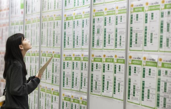 취업박람회를 찾은 한 여성 구직자가 채용일정을 확인하고 있다. ⓒ이정실 사진기자