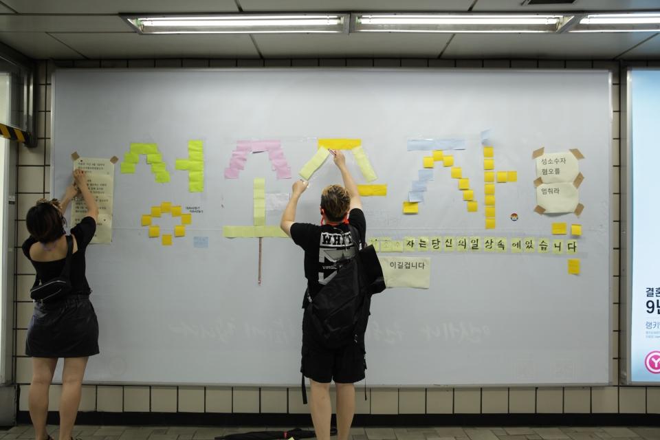 지난 8월 3일 오후 서울 마포구 신촌역에 게시됐던 성소수자 차별 반대 광고판이 훼손되자 시민들이 포스트잇으로 '성소수자'라는 글자를 복구하고 있다.