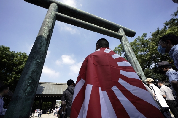 태평양전쟁 패전 75주년을 맞은 15일 일본 도쿄의 야스쿠니 신사에서 한 남성이 욱일기를 몸에 두르고 참배 순서를 기다리고 있다. 아베 신조 일본 총리는 야스쿠니 신사에 참배하진 않았으나 공물을 바친 것으로 알려졌다. Ⓒ뉴시스.여성신문