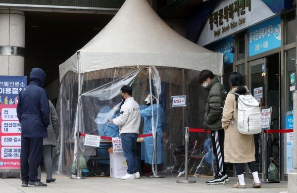 중등 임용고시를 하루 앞두고 노량진 대형 임용단기 학원에서 코로나19 확진자가 최소 32명 발생한 20일 서울 동작구 보건소에 마련된 선별진료소에 시민들이 코로나 검사를 받기 위해 대기하고 있다.