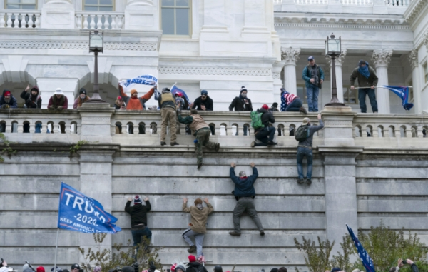 현지시간 6일 도널드 트럼프 미국 대통령의 지지자들이 워싱턴 미 국회의사당 벽을 기어오르고 있다. ⓒAP·뉴시스·여성신문