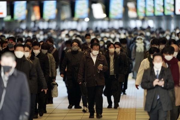 [도쿄=AP/뉴시스]8일(현지시간) 일본 도쿄의 한 기차역에서 마스크를 쓴 출근길 시민들이 몰려나오고 있다. 스가 요시히데 일본 총리는 도쿄를 비롯한 3개 현에 코로나19 확산을 막기 위한 긴급사태를 선포해 8일부터 발효됐다.