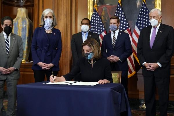 """낸시 펠로시 미 하원의장이 13일(현지시간) 의회에서 도널드 트럼프 대통령의 탄핵소추안에 서명하고 있다. 펠로시 의장은 """"오늘 하원은 그 누구도 법 위에 있지 않다는 것을 증명했다""""라고 하원의 탄핵소추안 가결을 평가했다. ⓒ뉴시스·여성신문"""