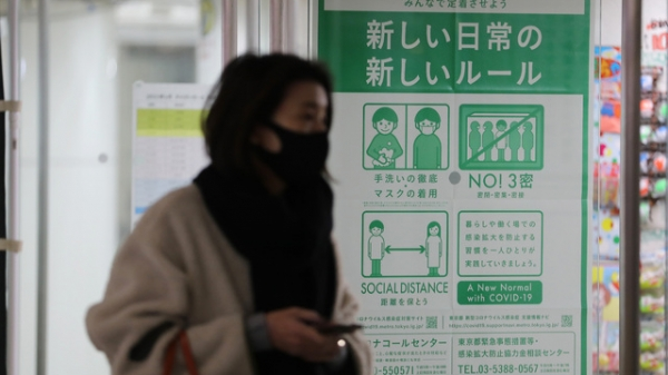 7일 일본 도쿄에서 마스크를 쓴 보행자가 코로나19 방지 관련 포스터 앞을 지나가고 있다. ⓒ신화∙뉴시스