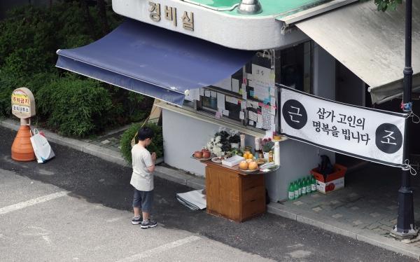 서울 강북구의 한 아파트 경비실 앞에 마련된 경비원 고 최희석씨를 위한 추모 공간에서 기도하고 있다. 아파트 관리직 노동자들은 입주민의 '갑질'에 시달려도 이를 직장 내 괴롭힘으로 신고할 수 없다. 고용관계가 없기 때문이다. ©뉴시스