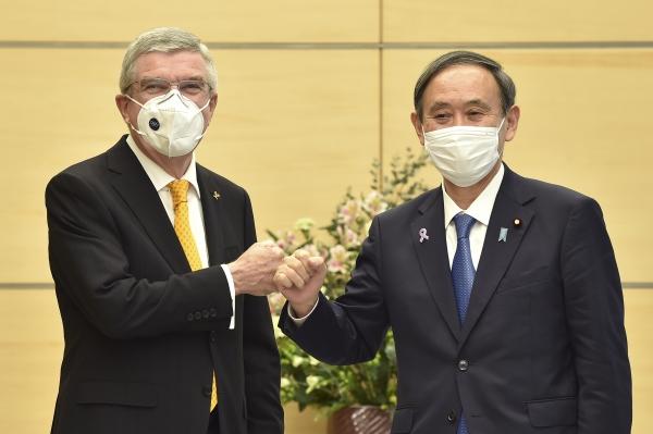 [도쿄=AP/뉴시스]일본을 방문한 토마스 바흐 국제올림픽위원회(IOC) 위원장(왼쪽)이 16일 오전 스가 요시히데 일본 총리(오른쪽)와 도쿄 총리 관저에서 만나 회담 전 주먹 인사를 나누고 있다. 2020.11.16.