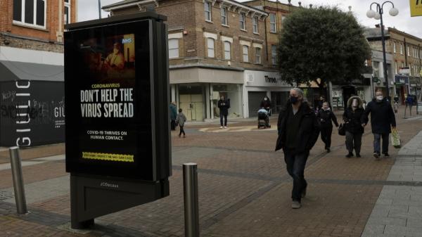 현지시간 19일 영국 런던 남서쪽 킹스턴에서 마스크를 쓴 시민들이 코로나19 안내판 부근을 걷고 있다. ⓒAP/뉴시스