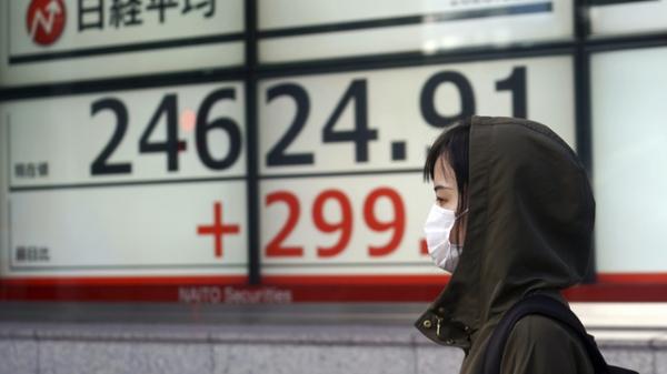 11월 9일 일본 도쿄 증권가에서 한 여성이 닛케이225 지수를 보여주는 전광판 앞을 지나고 있다. ⓒAP/뉴시스