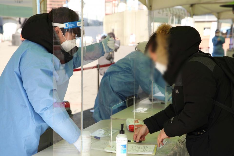 18일 오후 서울 중구 서울역 선별진료소에서 한 시민이 코로나19 검사를 받기 위해 역학조사서를 작성하고 있다. ⓒ홍수형 기자