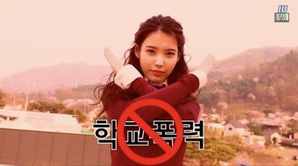 아이유의 유튜브 채널 'IU TV' 영상 중 아이유가 '학교폭력NO'라는 메시지를 전하는 모습. ⓒIU TV 영상 캡처