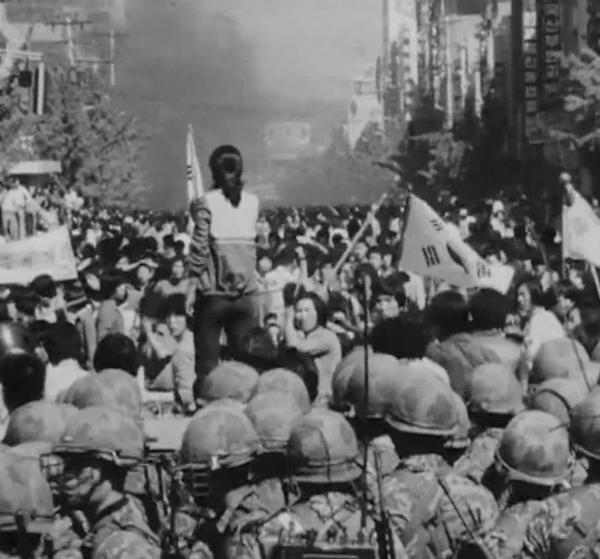 5·18 민주화운동 당시 대치하는 시민과 계엄군 사이에서 가두방송하는 전옥주씨의 뒷 모습. ⓒ5·18민주화운동기록관이 2018년 공개한 영상 캡처