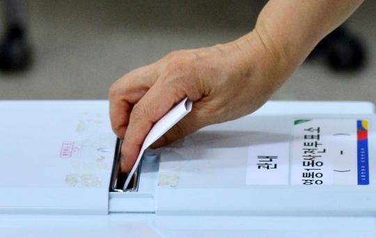 7·30 재보선 사전투표가 실시된 25일 유권자가 사전투표함에 투표하고 있다. ⓒ뉴시스·여성신문