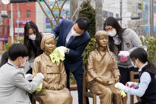 이승로 성북구청장과 계성고 학생들이 '한·중 평화의소녀상' 소녀들을 깨끗한 수건으로 꼼꼼히 닦아주며 환영하고 있다. ⓒ성북구청