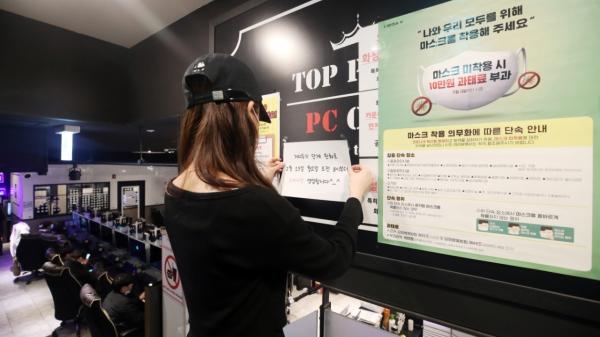 14일 오후 서울 시내 한 PC방에서 직원이 24시간 영업을 알리는 안내문을 부착하고 있다. ⓒ뉴시스