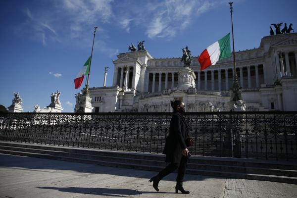 지난 8일(현지시간) 이탈리아 로마에서 이탈리아 내 코로나19 희생자를 기리는 국가 추모 행사가 열린 가운데 한 시민이 조기가 게양된 무명용사비 앞을 지나고 있다. 이탈리아의 코로나19 사망자는 10만3855명으로 집계됐다. ⓒ뉴시스·여성신문