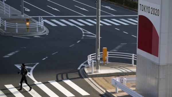 21일 일본 도쿄에서 코로나19 예방을 위해 마스크를 쓴 한 여성이 2020 도쿄올림픽 광고판 근처 건널목을 건너고 있다. ⓒAP/뉴시스
