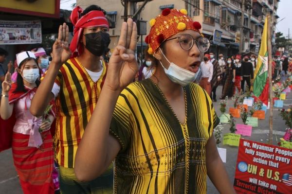 [양곤=AP/뉴시스]25일 미얀마 양곤에서 쿠데타 반대 시위대가 세 손가락 경례를 하며 구호를 외치고 있다. 미얀마 시위대는 24일 집 안에 머물며 상점 문을 닫는 등 '침묵시위'를 벌인 지 하루 만에 다시 거리로 나왔다.
