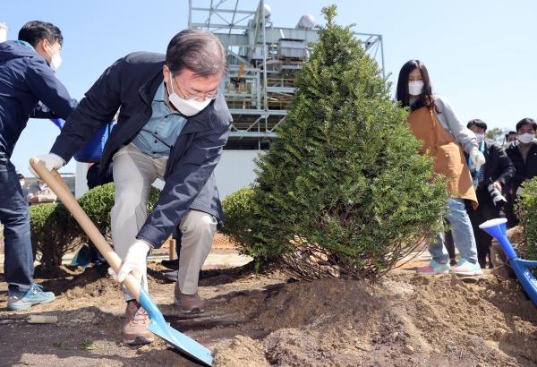 문재인 대통령이 5일 서울 마포구 서울복합화력발전소에서 열린 제76회 식목일 기념행사에서 상지초등학교 유채림 학생과 나무를 심고 있다. ⓒ뉴시스·여성신문