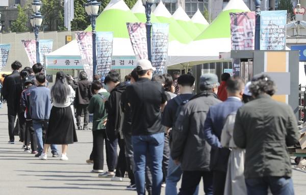 코로나19 신규 확진자가 주말 영향 등으로 닷새만에 700명 아래로 감소한 25일 오전 서울역 광장에 마련된 서울 중구 임시선별검사소에서 시민들이 검사를 받기 위해 줄지어 대기하고 있다. 이날 0시 기준 국내 누적 확진자는 전날보다 644명 증가한 11만8887명이다.