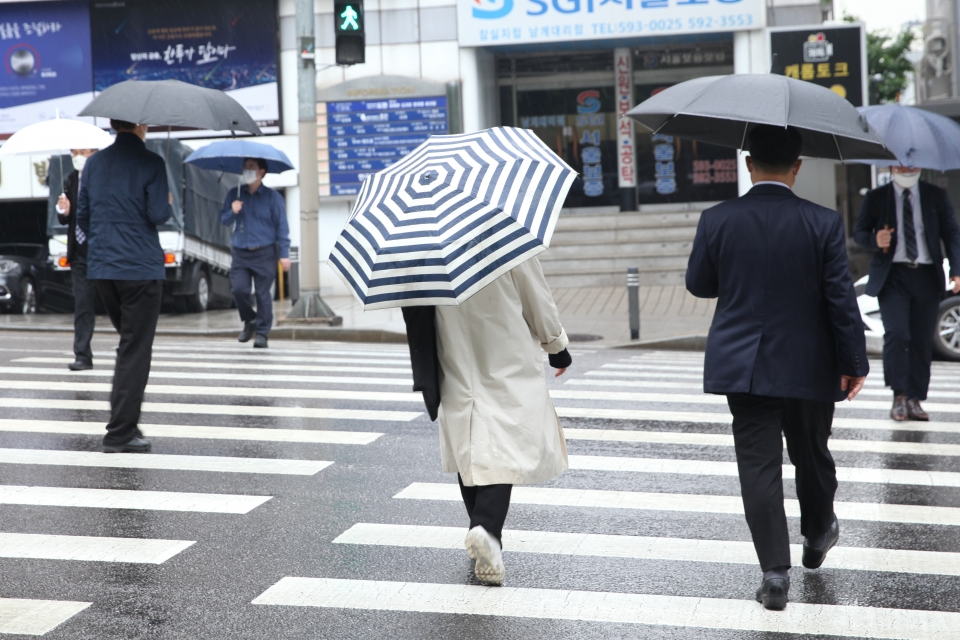 4일 오후 서울 서초구 한 신호 거리에서 시민들을 비를 피하기 위해 발걸음을 옮기고 있다. ⓒ홍수형 기자