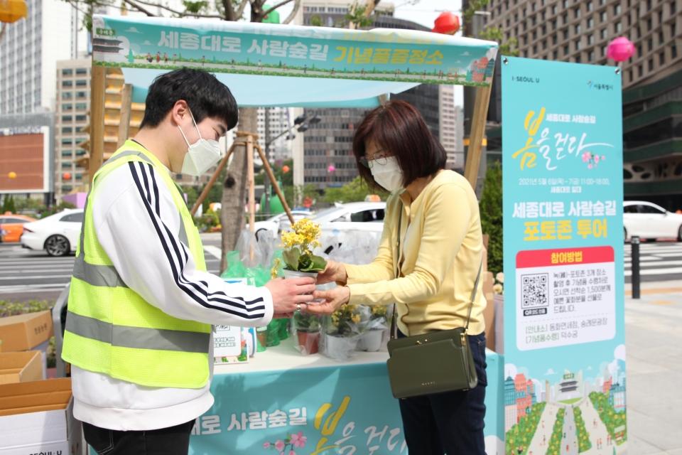 7일 서울 중구 세종대로 사람숲길 행사에서 한 시민은 포토 이벤트 참여하여 꽃을 받고 있다. ⓒ홍수형 기자