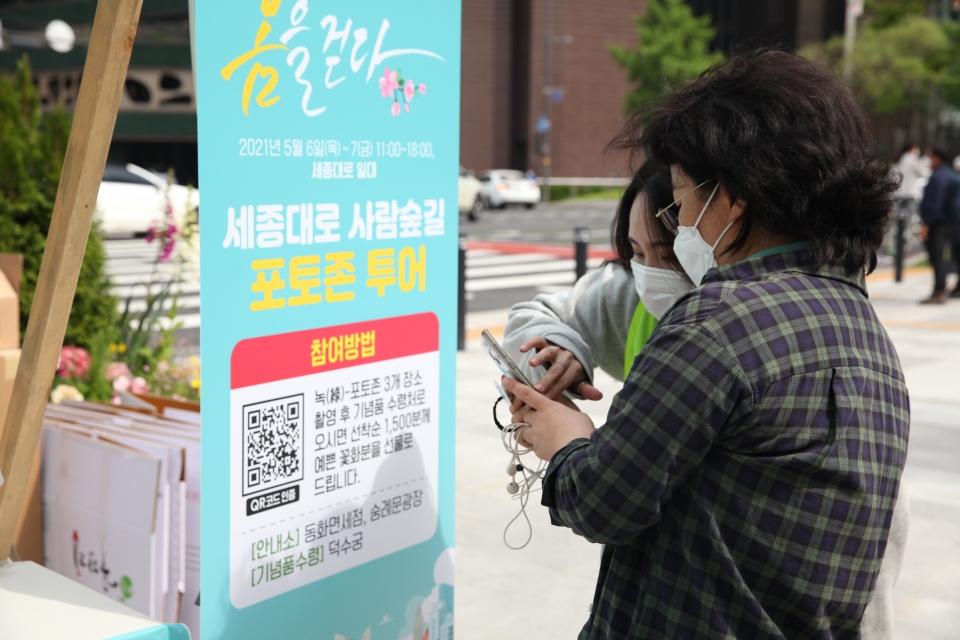7일 서울 중구 세종대로 사람숲길 행사에서 한 시민은 포토 이벤트 참여하여 방법 설명을 듣고 있다. ⓒ홍수형 기자