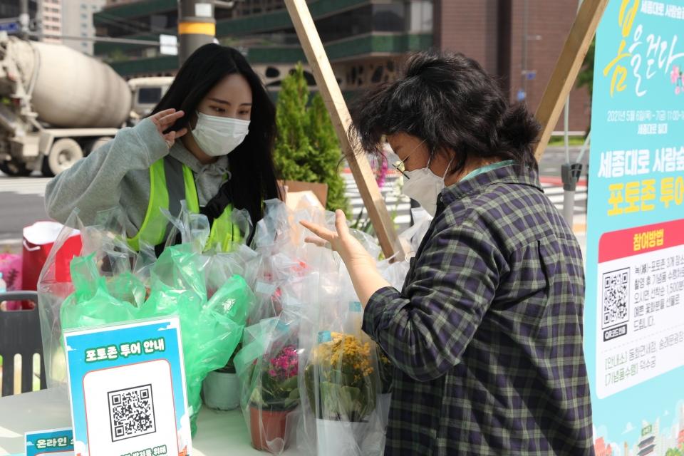 7일 서울 중구 세종대로 사람숲길 행사에서 한 시민은 포토 이벤트 참여하여 꽃을 고르고 있다. ⓒ홍수형 기자