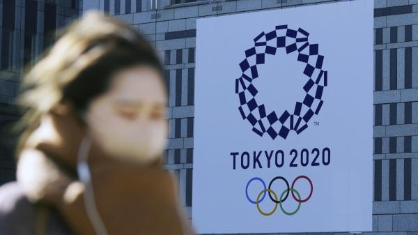 19일 코로나19 예방을 위해 마스크를 쓴 한 여성이 일본 도쿄에서 2020 도쿄 올림픽 현수막 근처를 걷고 있다. ⓒAP/뉴시스