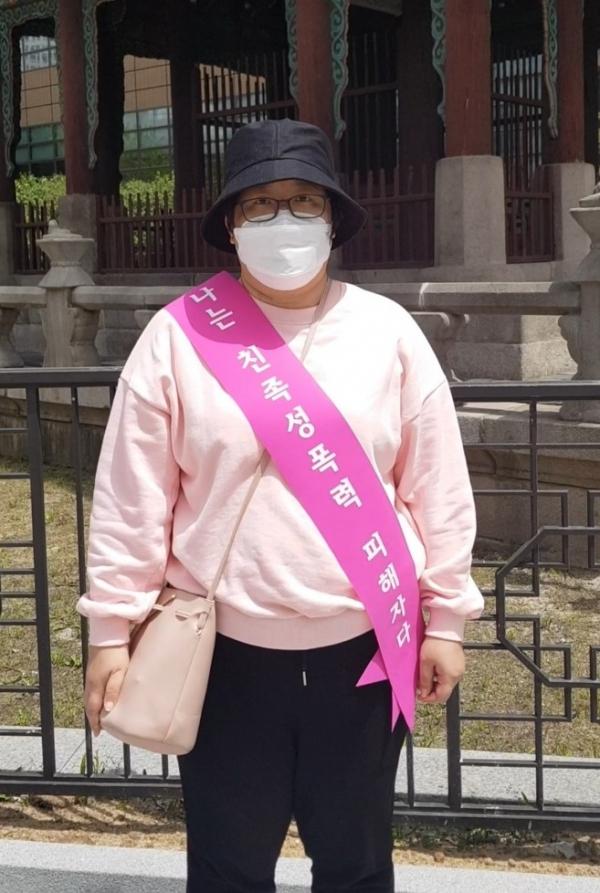 친족성폭력 생존자 '명아'는 5월8일 광화문 시위에서 '나는 친족성폭력 피해자다' 어깨띠를 둘렀다. ⓒ여성신문