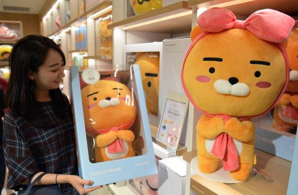 부산본점 7층 카카오프렌즈 매장에서 고객이 라이언 캐릭터 인형을 고르고 있는 모습.