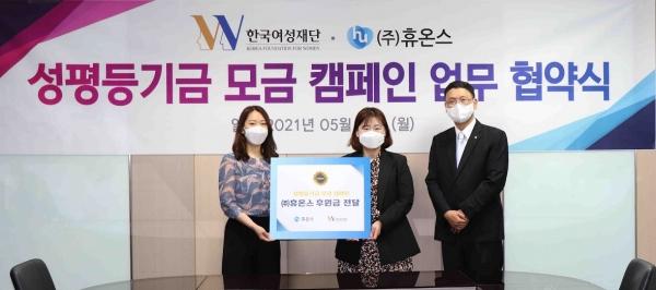 한국여성재단 관계자(왼쪽)와 휴온스 관계자가 전달식에 참석해 체결식을 진행했다. ⓒ한국여성재단