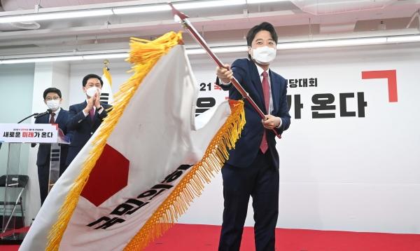 이준석 국민의힘 새 대표가 11일 서울 영등포구 여의도동 국민의힘 당사에서 열린 전당대회에서 당기를 흔들고 있다. ⓒ뉴시스·여성신문
