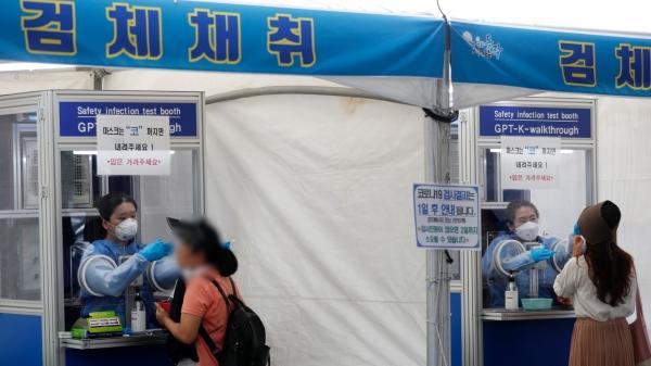 전국 대부분 지역에 폭염 특보가 발효된 13일 서울 동작구청 주차장에 마련된 임시 선별검사소에서 의료진들이 검체를 채취하고 있다. ⓒ뉴시스