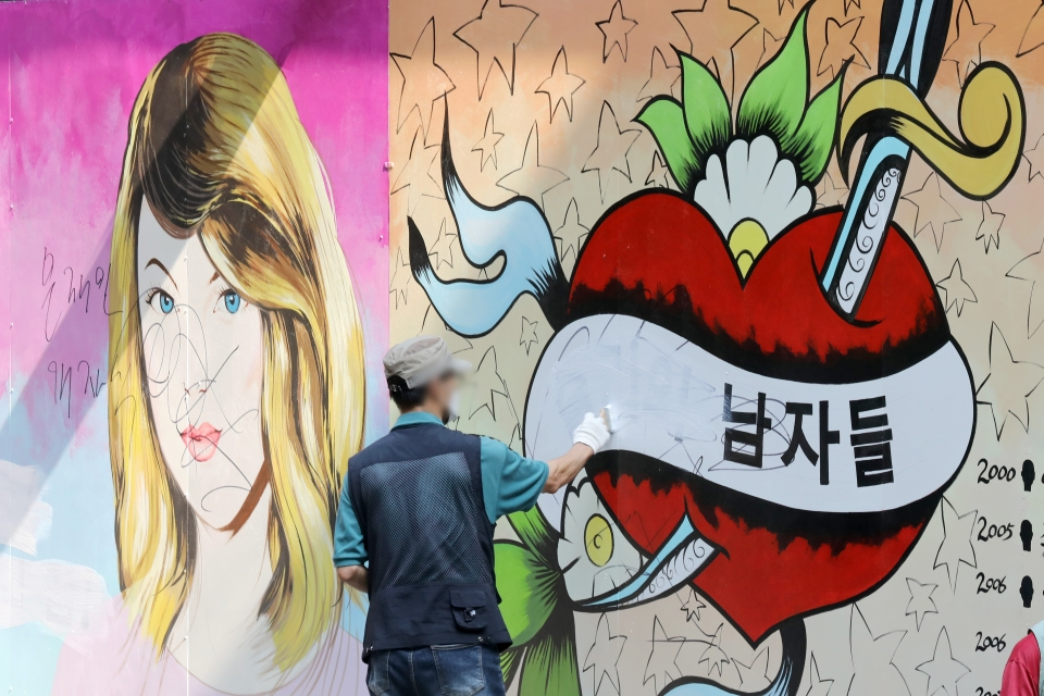 30일 오전 서울 종로구 윤석열 전 검찰총장의 아내 김건희 씨를 비방하는 내용의 벽화가 그려진 서점 외벽에서 서점 관계자가 벽화 속 문구를 지우고 있다.   ©뉴시스·여성신문