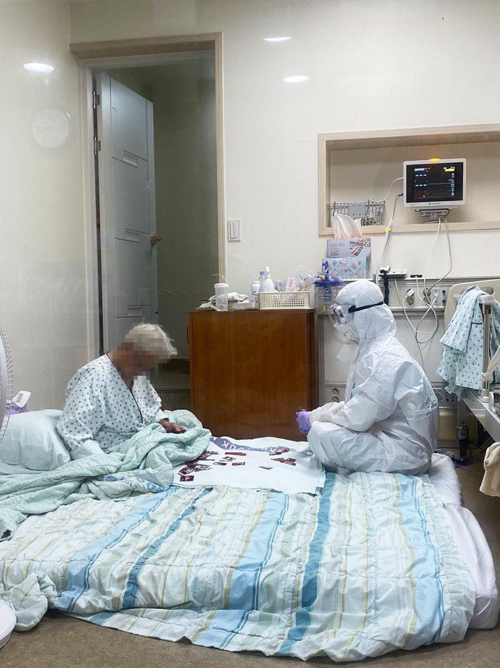 코로나19현장스토리 2차 공모전 사진 출품작. 방호복을 입은 삼육서울병원 이수련 간호사가90대 할머니과 화투를 활용한 그림 맞추기 놀이를 하고 있다.사진=대한간호협회 제공