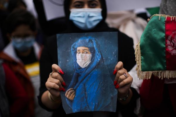 18일(현지시간) 벨기에 수도 브뤼셀에 있는 유럽연합(EU) 본부 밖에서 탈레반의 아프가니스탄 장악에 반대하고 경각심을 일깨우는 시위가 열렸다. 시위에 참여한 한 여성이 아프가니스탄 여성의 사진을 들고 있다. ⓒAP/뉴시스