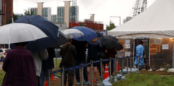 7일 오전 서울 용산역에 마련된 임시선별진료소에서 우산을 쓴 시민들이 코로나19 검사를 받기 위해 길게 줄지어 서 있다.