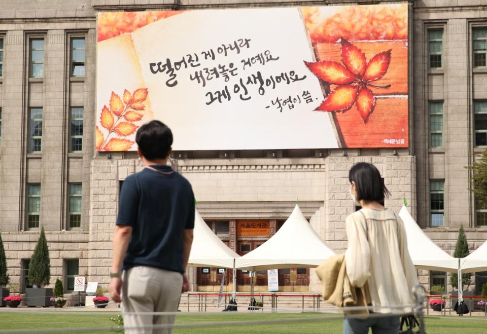 17일 서울 중구 서울도서관 외벽에 떨어진게 아니라 내려놓은 거예요 그게 인생이예요' 라고 쓰인 현수막이 붙어 있다. ⓒ홍수형 기자